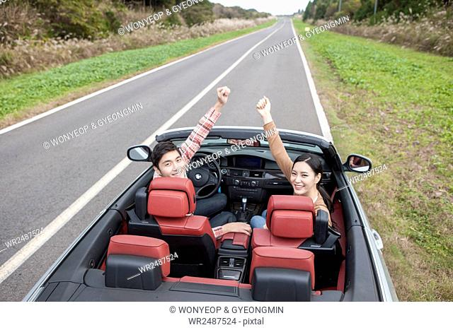 Side view of young couple in a car raising arms looking back