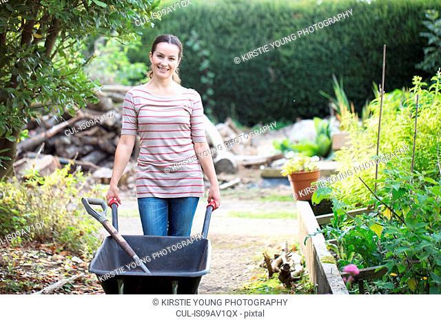 Portrait of female gardener pushing wheelbarrow in rustic organic garden