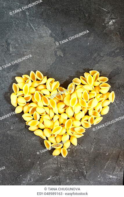 Raw macaroni - pasta Conchiglie. In the middle of the empty space in the shape of a heart on a dark concrete background