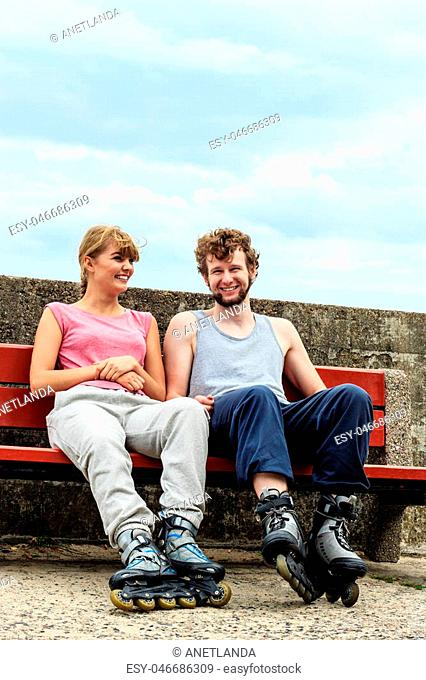 Young people friends in training suit with roller skates. Woman and man relaxing on bench outdoor