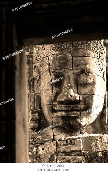 Stone carving of a face on wall at Khmer Kingdom palace ruins