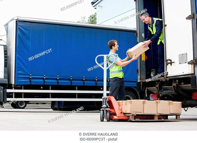 Two men unloading cardboard boxes from truck