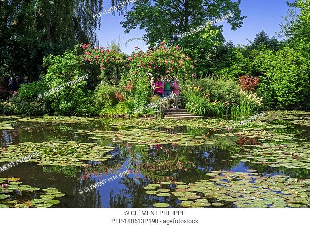Tourists visiting the Water Lily Pond in summer, garden at the home of Impressionist painter Claude Monet in Giverny, Eure, Normandy, France