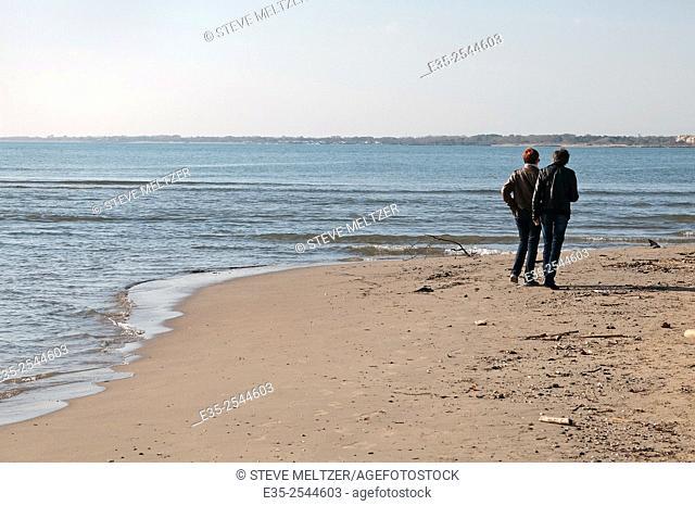 Two friends walk along a Mediterranean beach in autumn