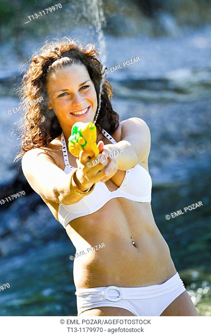 Beautiful young woman on the beach with a plastic pistol blasting water