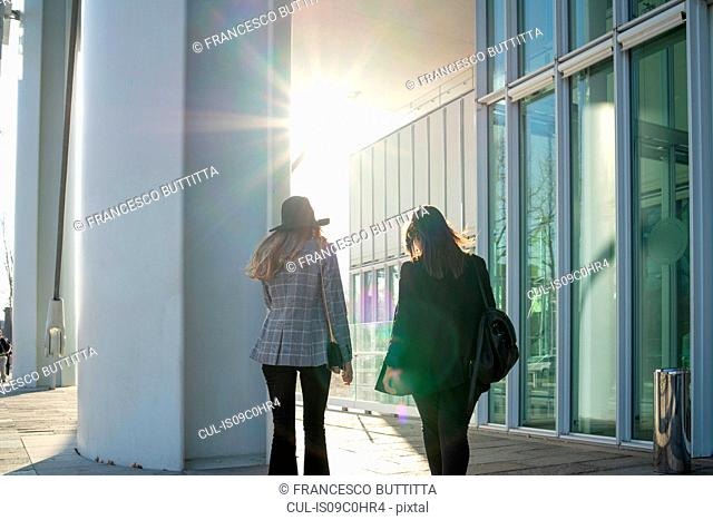 Young women strolling outside office building, rear view, Turin, Piemonte, Italy