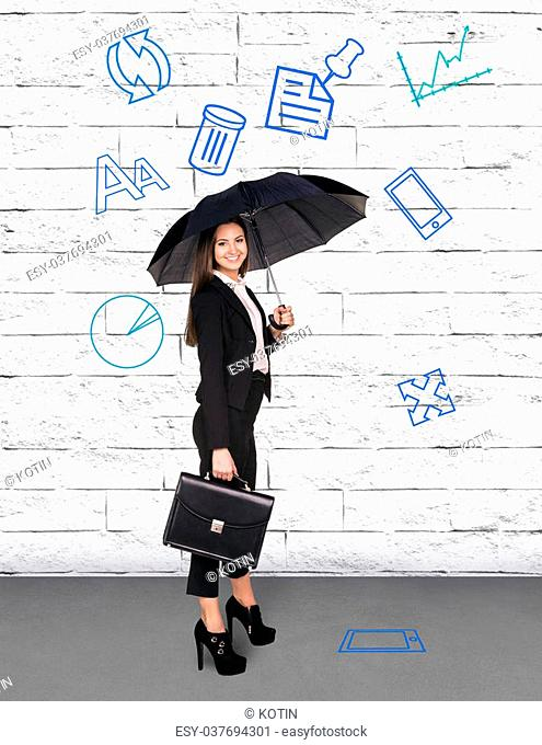 Pretty businesswoman holding umbrella on white wall background