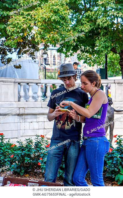 A young couple look at an used book at a vendor stand outside in a park in Mount Vernon at the Baltimore Book Festival, Baltimore, Maryland, 2013