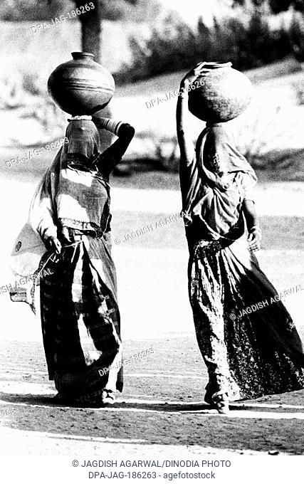 Women balancing pots Doli Bishnoi village Jodhpur Rajasthan India Asia 1984
