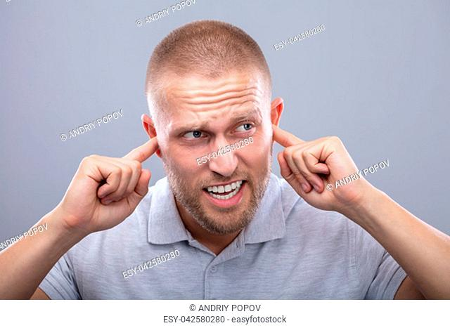 Young Man Disturbed By Noise Covering His Ears With Finger