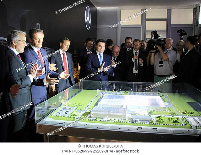Markus Schafer (2nd from left), from Mercedes-Benz Cars, and his guests look at a model during the groundbreaking ceremony of a new Mercedes plant at the...