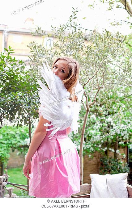 Teenage girl wearing angel wings