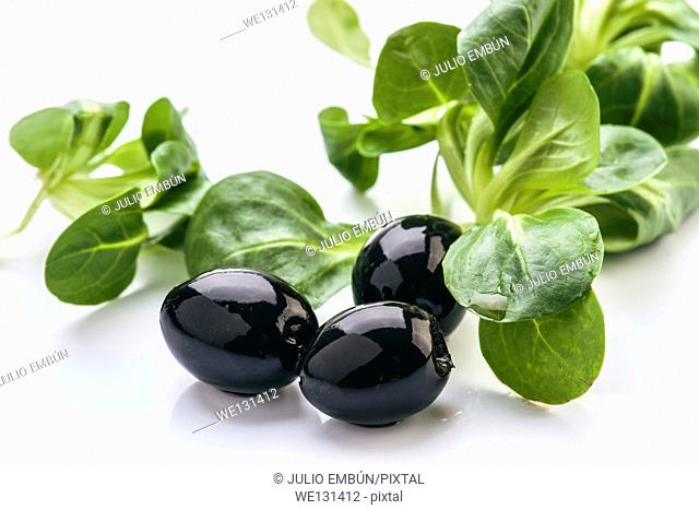 Black olives and salad leaves isolated on white