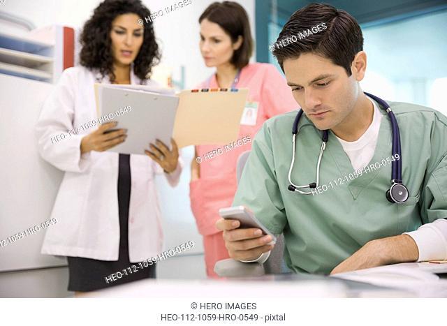 Nurse using smart phone in clinic