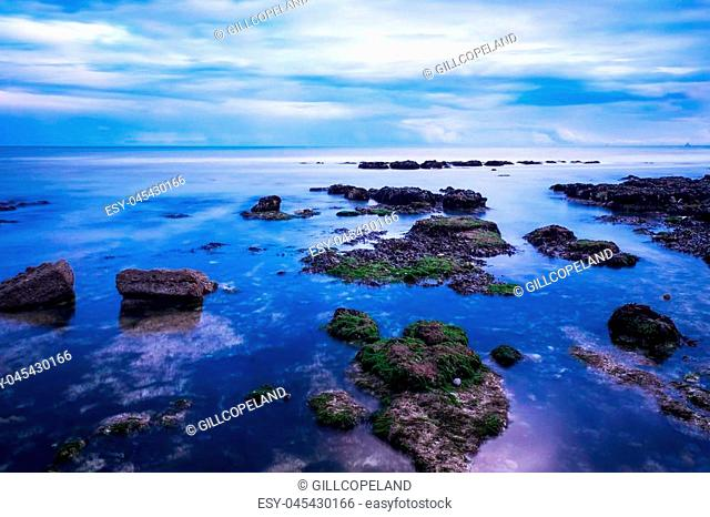 calm blue sea water surrounding small rocks in the foreground, the sea ends at the horizon and the sky fills the top half of the image