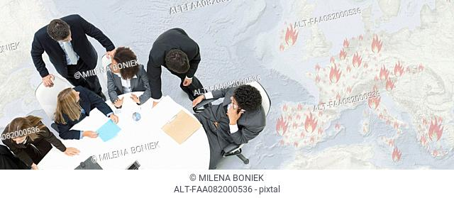 Executives in meeting, large map depicting European economic crisis in background