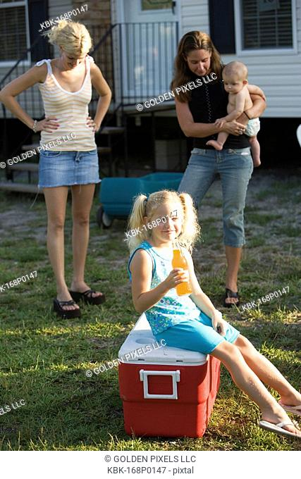 Young women and children in front of trailer home