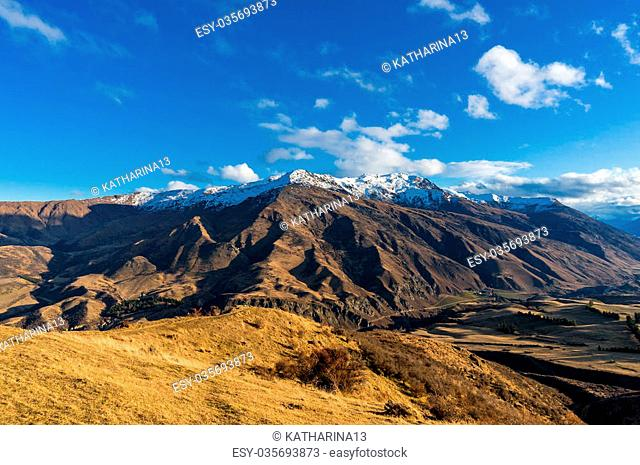 Epic mountain valley landscape. Aerial scenic valley view from Crown Range road, Queenstown, New Zealand. Mountain road to Queenstown