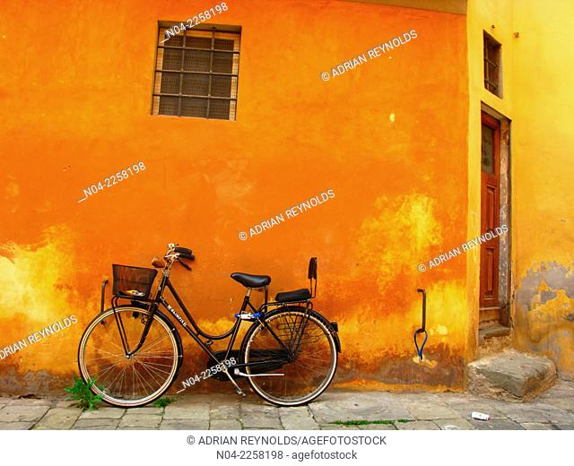 Bicycle propped against an orange colored wall in Pistoia, Tuscany