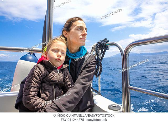 four years old blonde girl looking at with dislike expression face, in arms of her mother, sitting on the stern of motorboat sailing in Strait of Gibraltar