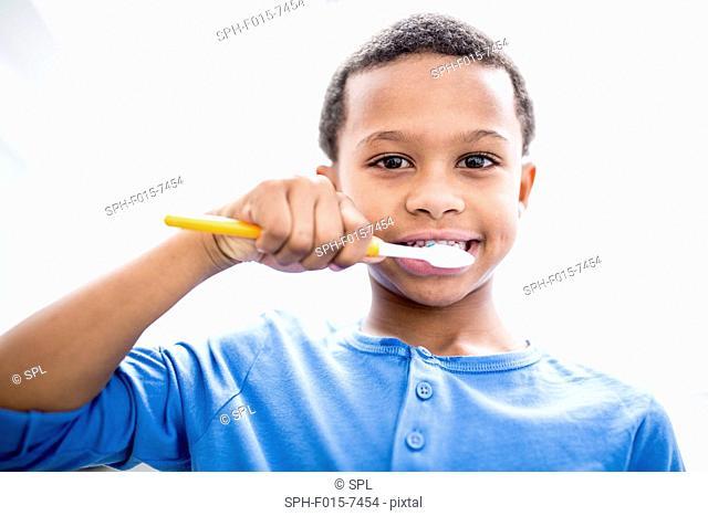 MODEL RELEASED. Boy brushing teeth, portrait, close-up