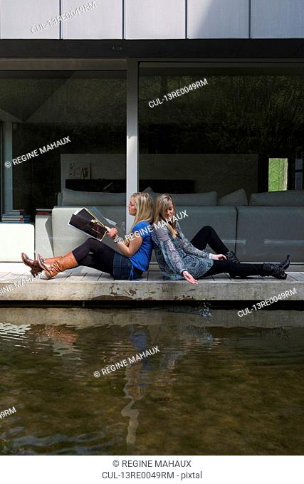 teenages reading a magazine near water