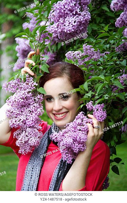 A young woman with lilacs in Spokane, Washington, USA