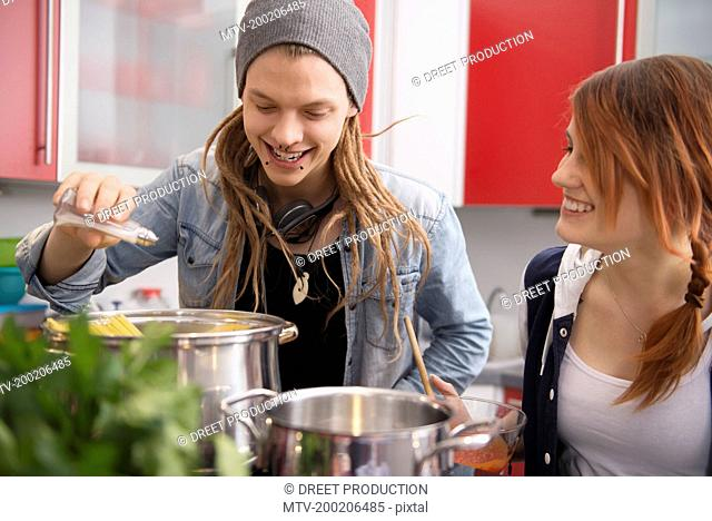 Young couple cooking together in kitchen, Munich, Bavaria, Germany