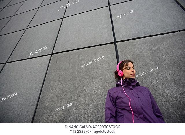 Attractive young woman listening to music with pink headpones, surrounded by modern architecture