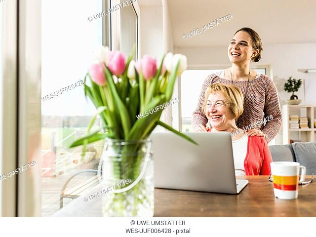 Happy young woman with senior woman at table with laptop
