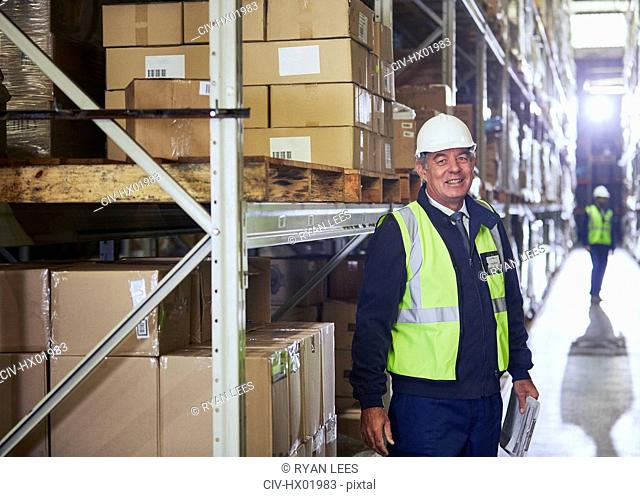 Portrait smiling manager with clipboard next to shelf in distribution warehouse