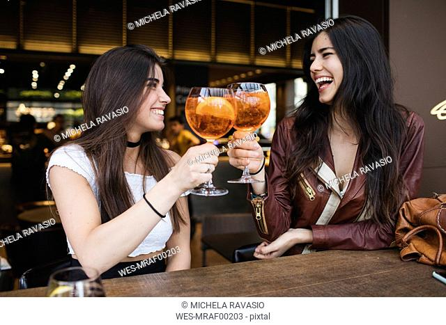 Two happy young women toasting in a bar
