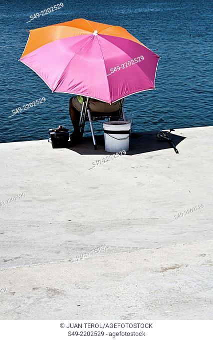 Man fishing in a riverbank, Valencia, Spain