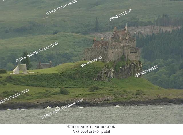 GV, MS, from boat, rocky green coastline, woodland, scottish castle on coast, tranquil, picture postcard. Mull, Scotland, UK
