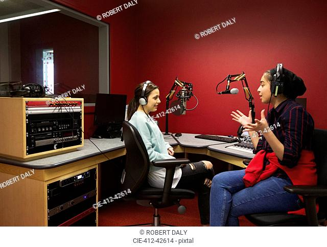 Teenage musicians recording music in sound booth