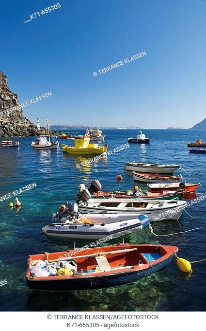 Colorful fishing boats in Ammoudi Bay near Oia Thira, on the Greek Island of Santorini, Greece