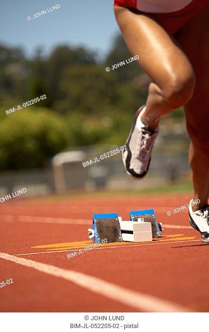 Female runner leaving starting blocks