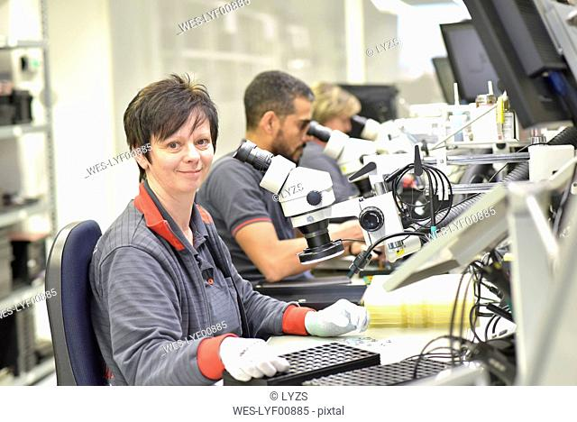 Portrait of smiling woman working on quality control in the manufacturing of circuit boards for the electronics industry