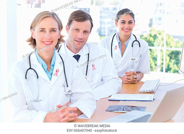 Composite image of smiling doctors posing at their desk