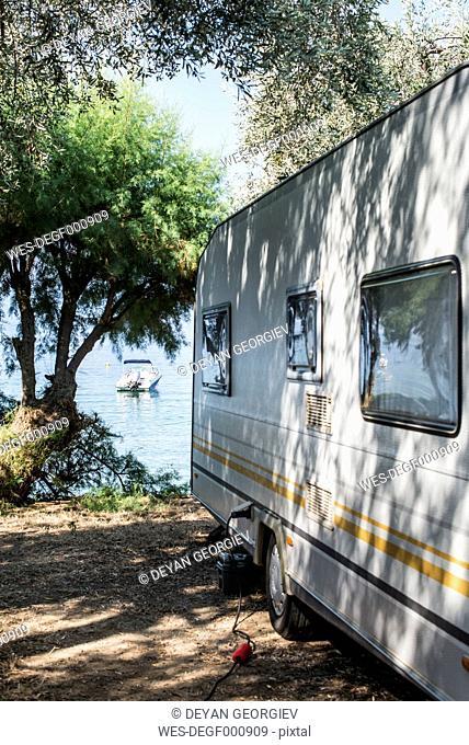 Greece, Kala Nera, caravan under olive tree at the sea