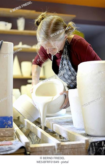 Woman pouring liquid into mold in porcelain workshop