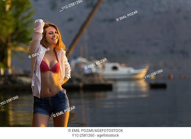 Pretty teen girl posing sidelighted by sunset warm light