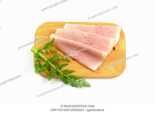 ham slices with dill rolled on wooden cutting board