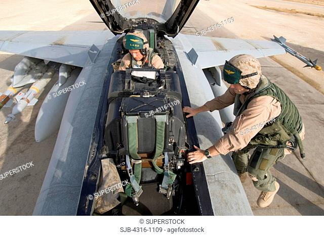 US Marine Corps Aviators Climb Into the Cockpit Of Their F/A-18D Hornet at Al Asad Air Base in the Al Anbar Province of Iraq To Begin a Close Air Support...