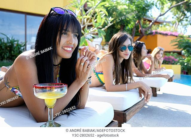 Four attractive and pretty women in bikinis enjoying a day at a swimming pool with cocktails