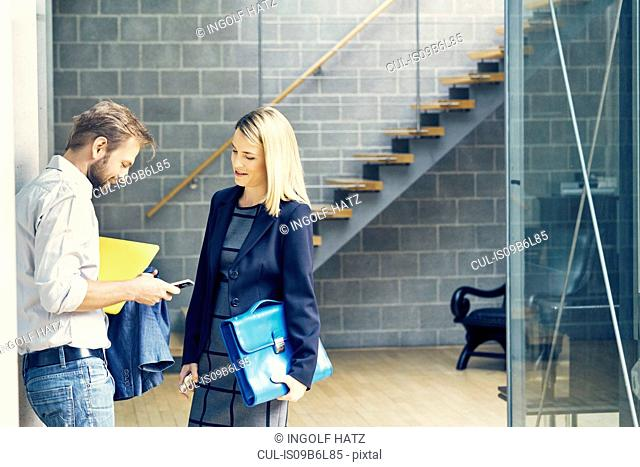 Businessman and woman looking at smartphone in open plan office