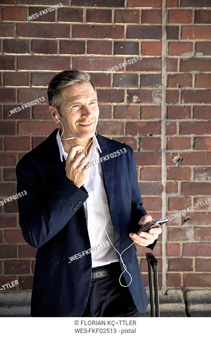 Mature businessman with earphones and smartphone at brick wall