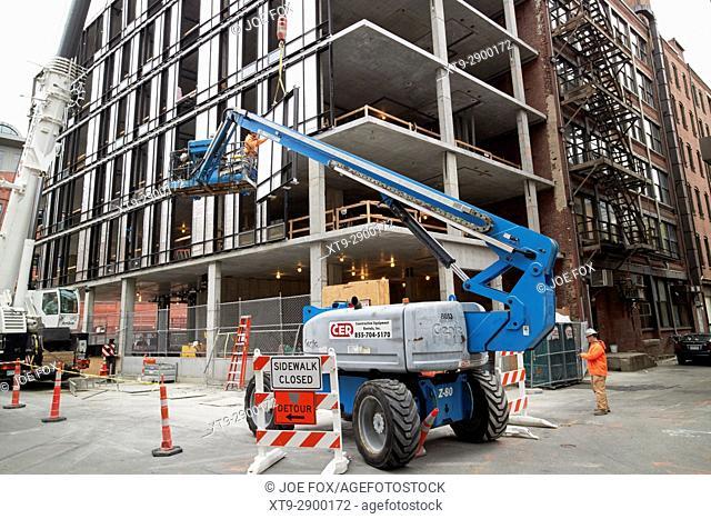 cherry picker elevated platform guiding building panels on construction site Boston USA