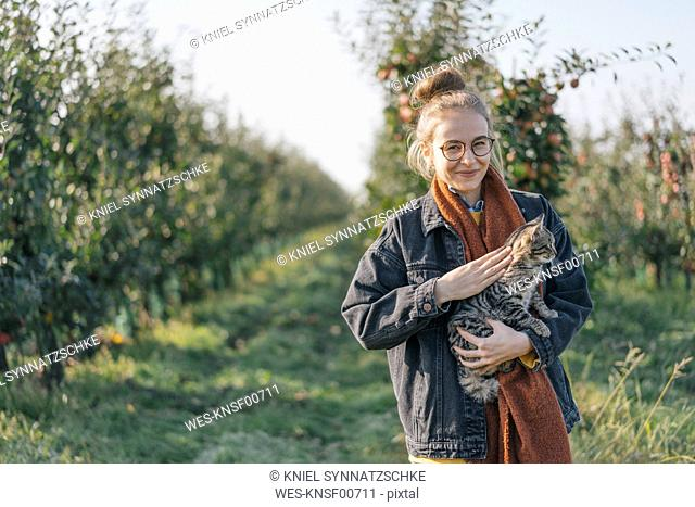 Young woman holding a cat in apple orchard