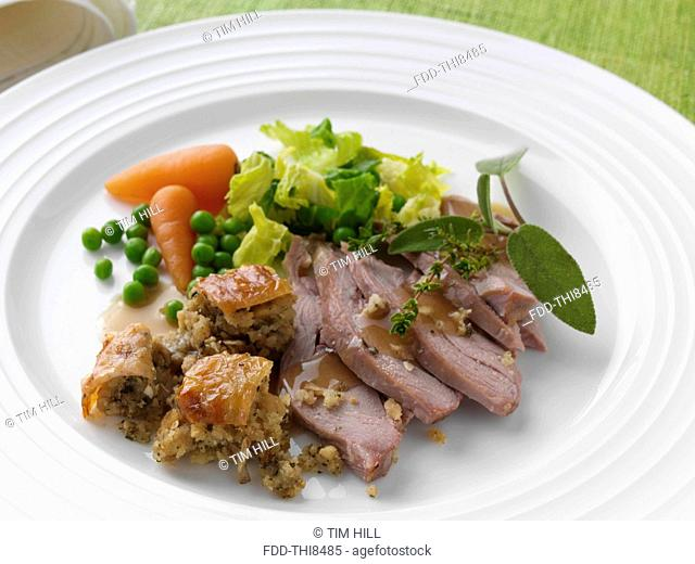 Roast turkey thigh with stuffing carrots cabbage peas and gravy